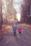 Mom and Baby Daughter with Teddy Walking on Gravel Stock Images