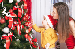Mom with baby decorating a christmas tree Stock Image