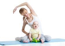 Young mom with baby doing gymnastics and fitness exercises Royalty Free Stock Photos