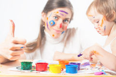 Mom and baby draws with colored inks Royalty Free Stock Photos
