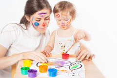 Mom and baby draws with colored inks Stock Photos