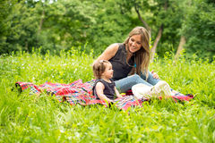 Mom and baby girl on picnic. In park stock photography