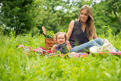 Mom and baby girl on picnic in park. Sitting on plaid blanket royalty free stock photos