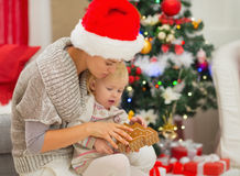 Mom and baby girl playing near Christmas tree Stock Images