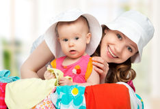 Mom and baby girl with suitcase and clothes ready for traveling. Mom and baby girl with suitcase baggage and clothes ready for traveling on vacation Royalty Free Stock Images