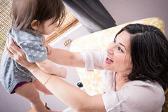 Mom and Baby. Mom happily flying her baby into the air Royalty Free Stock Photo