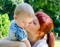 Mom and Baby. Mom and her beloved baby hugging in the park stock images