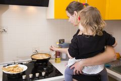 Mom with baby in his arms preparing food in the kitchen. Housewife with children. stock photography
