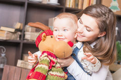 Mom with baby holding toy of big elk! Stock Photo