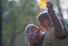 Mom and baby looking at the yellow maple leaf. On outdoors Royalty Free Stock Image