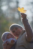 Mom and baby looking at the yellow maple leaf. On outdoors Stock Image