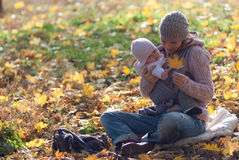 Mom and baby looking at the yellow maple leaf. On outdoors Royalty Free Stock Photo