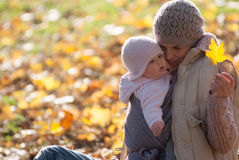 Mom and baby looking at the yellow maple leaf. On outdoors Royalty Free Stock Photos