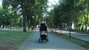 Mom with baby, lying in a stroller on an evening walk. Urban landscape.