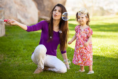 Mom and baby making some bubbles. Beautiful young Hispanic mother and her baby girl having fun with bubbles outdoors Stock Image