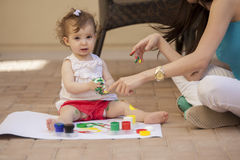 Mom and baby painting outdoors Stock Photography