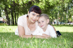 Mom and baby in park. The portrait of the baby and mother in the park, on the green grass Stock Images