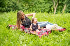 Mom and baby on a plaid blanket. In nature royalty free stock photography