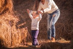 Mom and baby play together in the open air in the afternoon. games in nature. farm days. giant haystack and family on it. Pediatric hyper activity and royalty free stock photo
