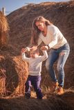 Mom and baby play together in the open air in the afternoon. games in nature. farm days. giant haystack and family on it. Pediatric hyper activity and stock image