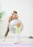 Mom and baby playing with fitness ball. In gym Royalty Free Stock Photography