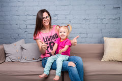 Mom and baby are playing and having fun in the room on the couch. They are dressed in bright clothes. Attractive, stylish and youn royalty free stock photos