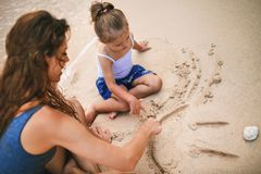 Mom and baby playing near beach. Traveling with family, child. Mom and baby playing near the beach. Traveling with your family, child. Games with child affect Stock Images