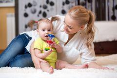Mom and baby playing toy at home Stock Photos