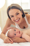 Mom and baby. Portrait of beautiful young mom and her sweet little baby looking at camera and smiling, lying on bed at home Royalty Free Stock Image