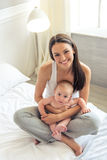 Mom and baby. Portrait of beautiful young mom and her sweet little baby looking at camera and smiling, sitting on bed at home Royalty Free Stock Photo