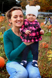 Mom and Baby in pumpkin patch. A sweet baby wearing a white sock hat and a mommie are in a pumpkin patch sitting on a large pumpkin. Shallow depth of field royalty free stock photo