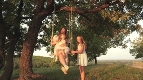 Mom and baby ride on a rope swing on an oak branch in forest. Family fun in park, in nature. warm summer day. mother stock video footage