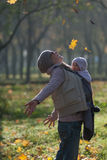 Mom and baby in a sling rejoice falling autumn leaves. Outdoors royalty free stock photography