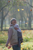 Mom and baby in a sling rejoice falling autumn leaves. Outdoors stock photos