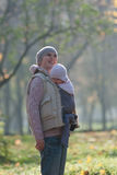 Mom and baby in a sling rejoice falling autumn leaves. Outdoors royalty free stock photo