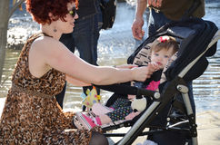 Mom with Baby in Stroller. A mom with her one year old baby in a stroller in a park. Mom packing up baby stuff with stroller Royalty Free Stock Image