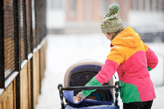 Mom and baby in stroller on walk, snowy winter weather. Snowfall, blizzard, outdoor. Mom and baby in a stroller on a walk in the snowy winter weather. Snowfall royalty free stock images
