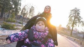 Mom with a baby in a stroller walks in a park in early spring between puddles of melting snow in the background of the. Sunset, evening stock video
