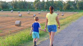 Mom and baby take a selfie walking along the pathway near hay bales