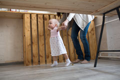 Mom and Baby Toddler girl first steps, lifestyle real interior, Stock Image