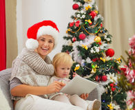 Mom and baby using tablet PC near Christmas tree Stock Images