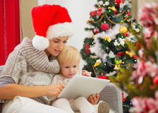 Mom and baby using tablet PC near Christmas tree Royalty Free Stock Image