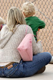 Mom and Baby watching baseball game on sidelines. Mom and Baby watching baseball game Stock Photo