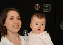 Mom and baby watching bubbles Royalty Free Stock Photos