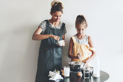 Mom baking with her daughter. Mom with her 10 years old daughter dressed in linen aprons are cooking together over light wall, lifestyle photo series Stock Image