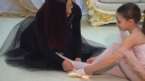 Mom ballerina wears Pointe shoes to my daughter. Young attractive ballerina with mother.,slow motion stock video
