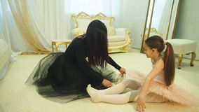 Mom ballerina wears Pointe shoes to my daughter. Young attractive ballerina with mother stock footage