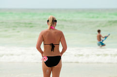 Mom in bikini swimsuit from behind at the beach. Stock Images