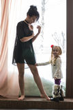 Mom in black dress and little girl Stock Photography