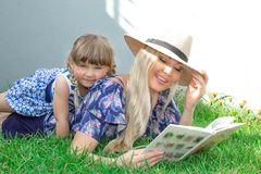 Mom blonde in a hat and her daughter are lying on the grass and reading a book, happy family. stock images